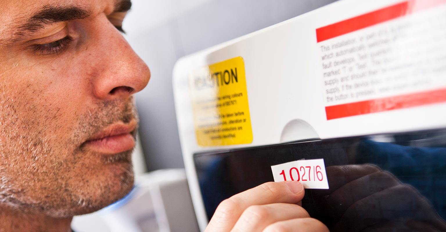 Man applying a label to a consumer unit