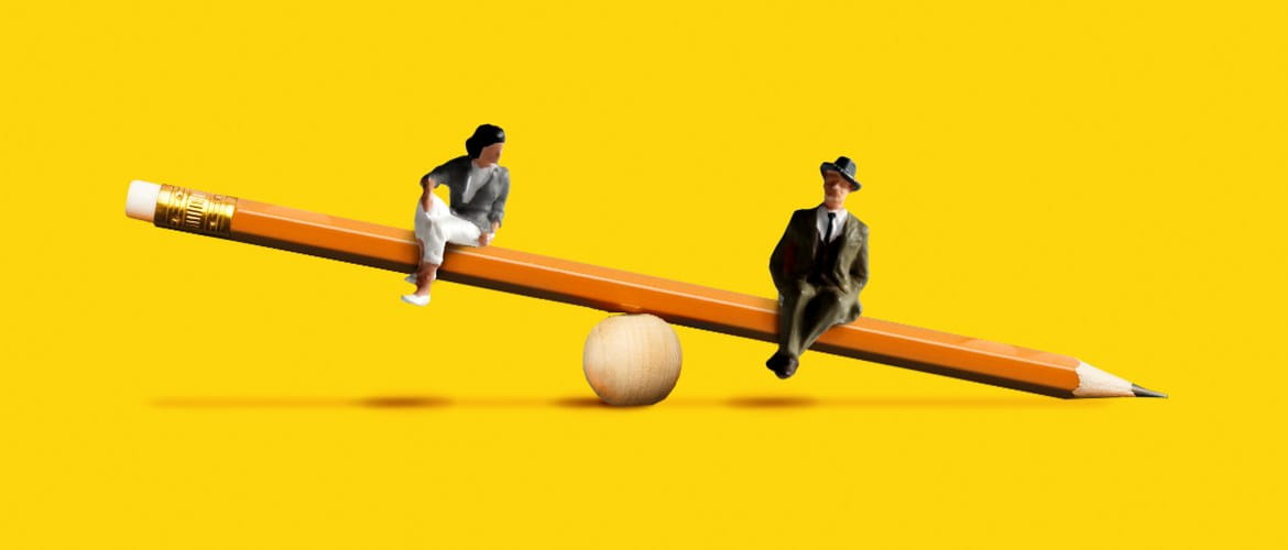 Two plastic people sitting on a pencil shaped seesaw. The male plastic model appears to be lower and heavier than the female.