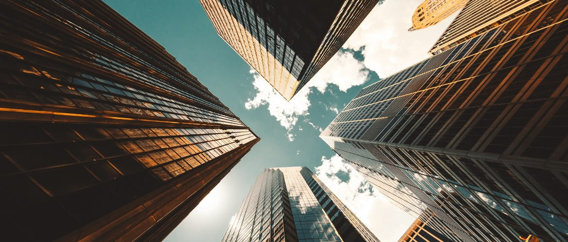 Office of the future image depicting skyscrapers in a city business district from the ground looking up to the sky during the day