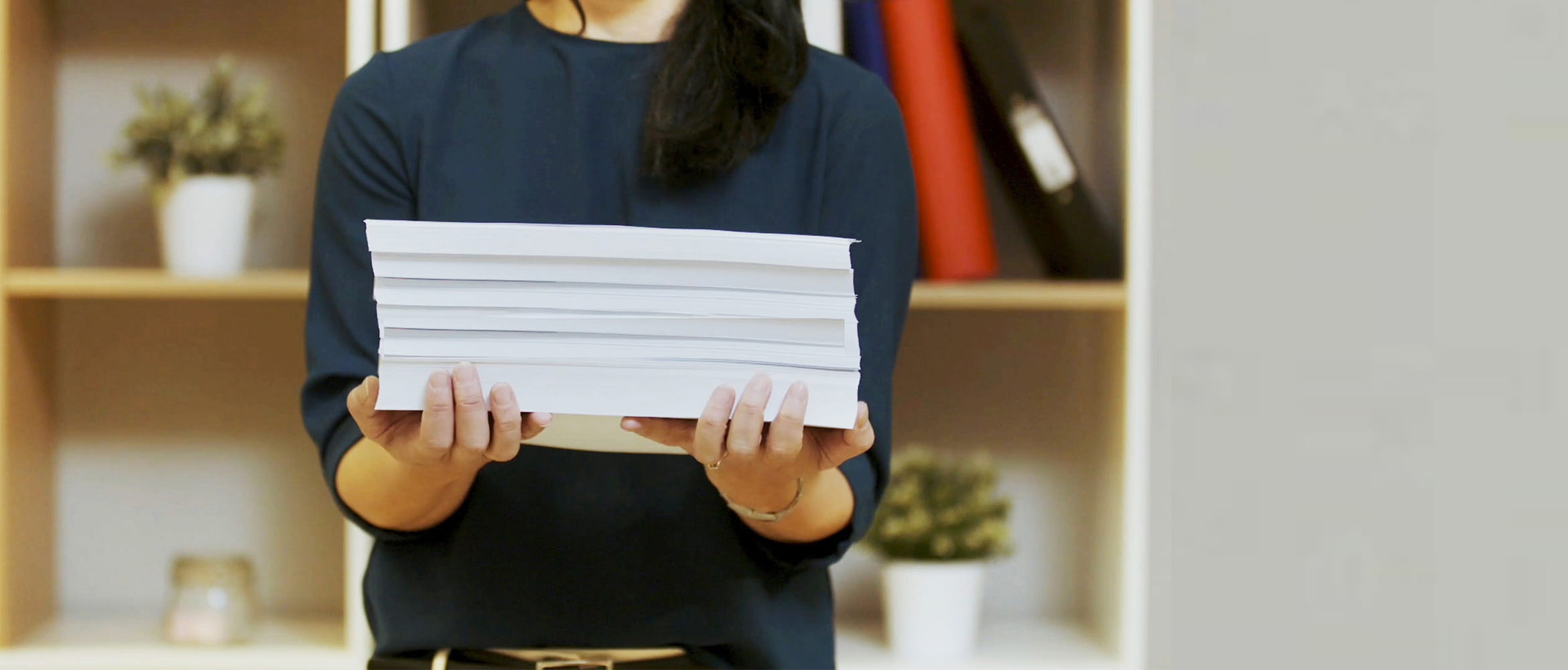 Woman holding pile of paper