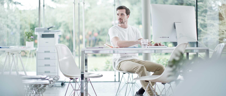 Mand sidder ved en computer med en printer i baggrunden