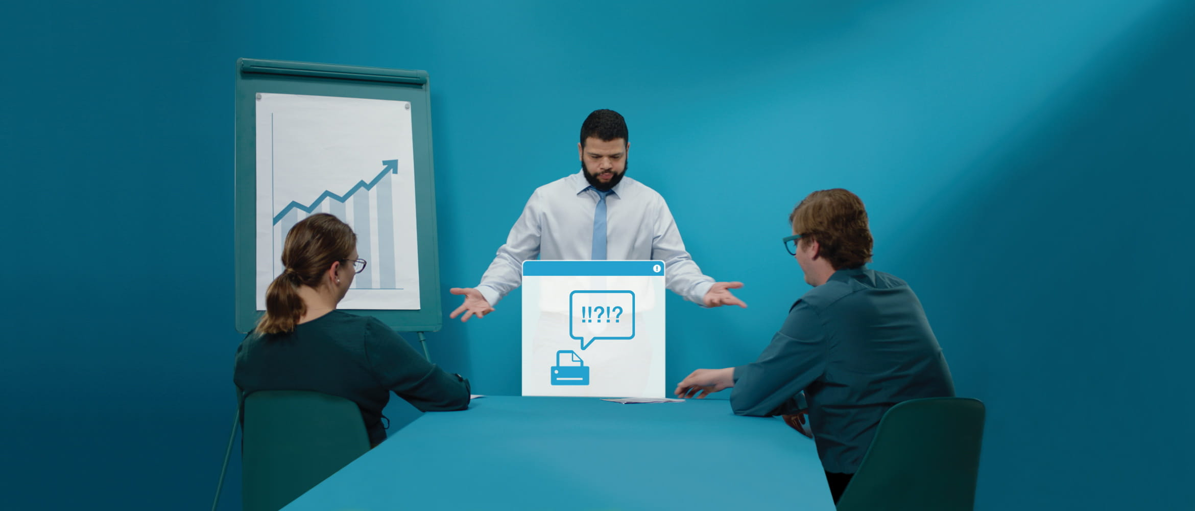 Man stood up doing a presentation to a man and woman