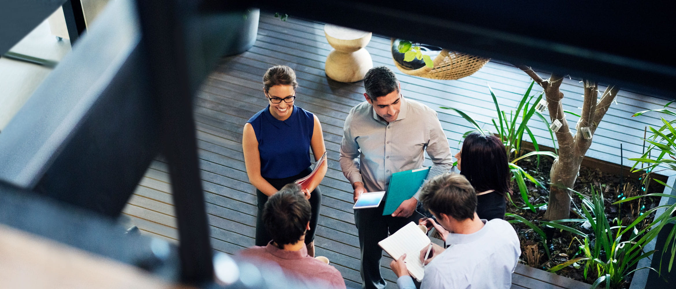 Five employees (two female and three male) in the workplace of the future are holding an informal stand-up business meeting in the office. The scene is pictured from overhead. The team if co-workers are holding files, notepads and tablet computers as they collaborate.