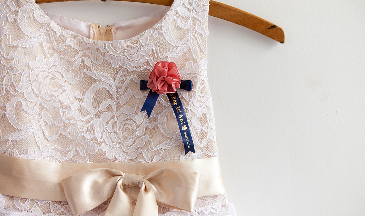 A bridesmaid's brooch pinned on their bridesmaid's dress, personalised with a Brother satin ribbon
