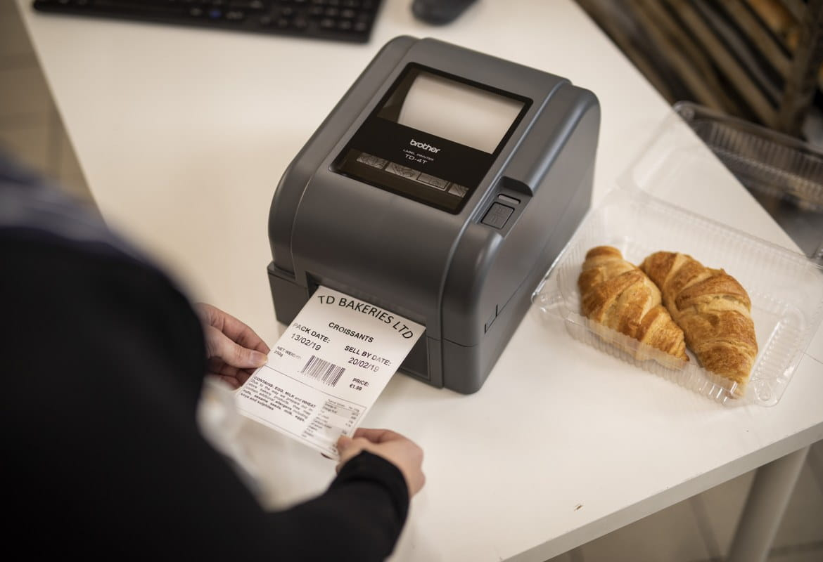 Close up a Brother label printer printing out a food day label for a pack of croissants in the back office of a food deli, bakery or cafe