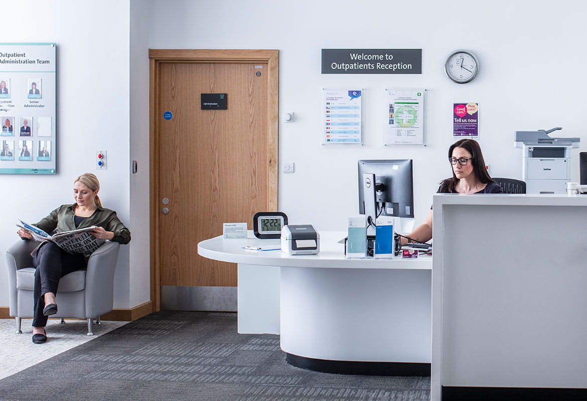 Female receptionist sat at desk using a computer, female patient sat reading newspaper