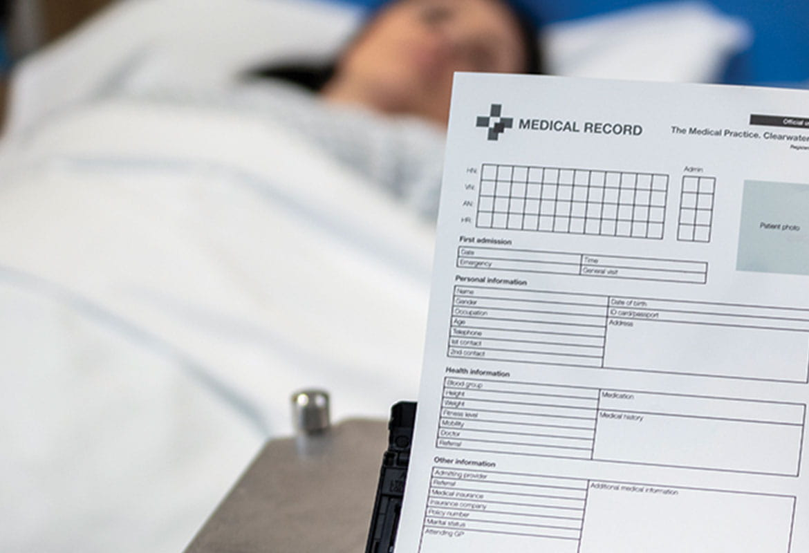 Female patient lying down in bed, Brother ADS-3600W scanner scanning patient document