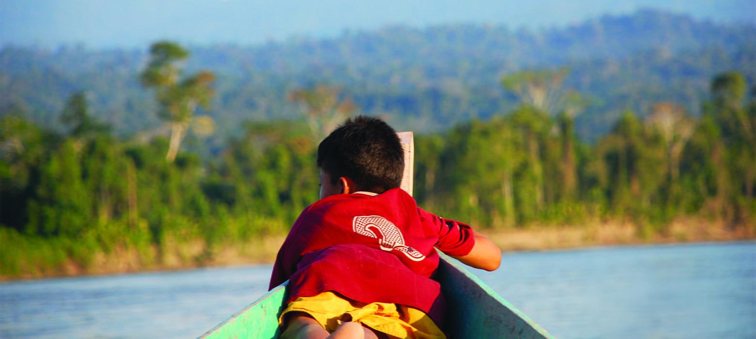 dreng ligger i båd på flod