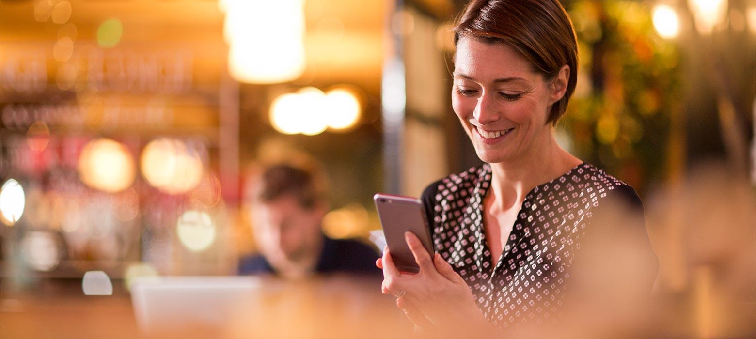 glad kvinde ser på mobil