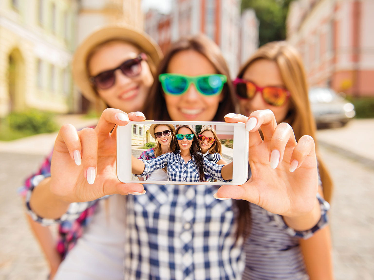 Three girls taking a selfie on an iPhone outdoors