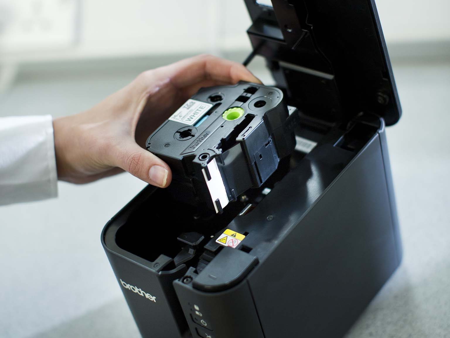 Brother TZe tape cassette being inserted into a PT-P900W label printer