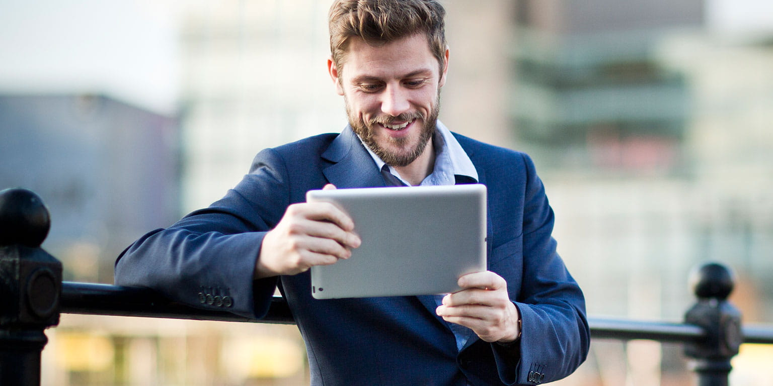 Mand sidder udenfor og læser om Brother på sin tablet