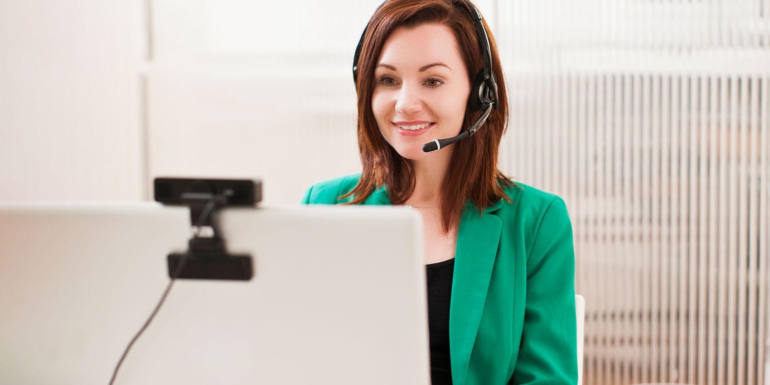 Dame med headset sidder i callcenter