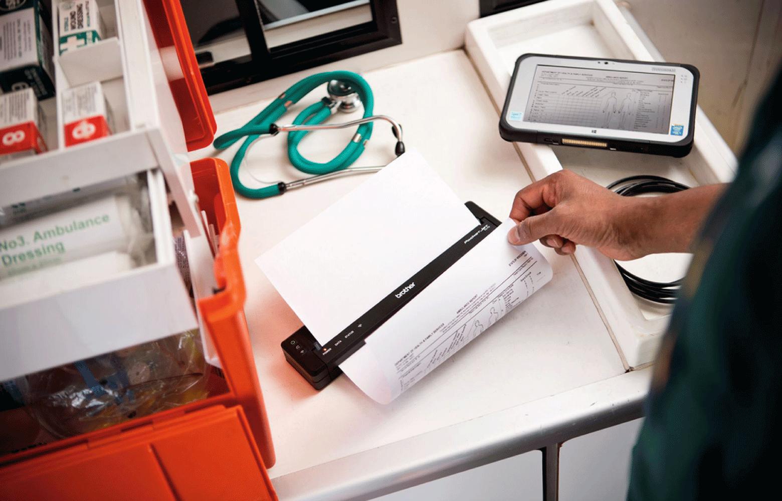 Person der printer fra en mobl printer på et bord