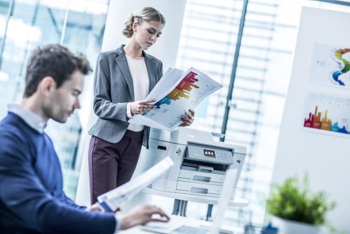 inkjet printer mand og kvinde ser på udskrifter