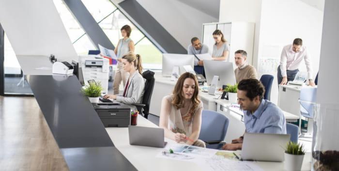 Kontorlandskab med medarbejdere, laptops og printere